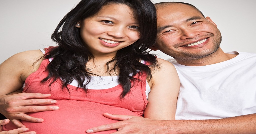 Happy expecting pregnant asian couple